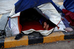 A migrant who has been camping out for months at the entrance to the Puerta Mexico international bridge, in Matamoros, Tamaulipas state, Mexico, rests in his tent as the day breaks, Thursday, June 27, 2019. Hundreds of migrants from Central America, South America, the Caribbean and Africa have been waiting for their number to be called at the bridge in downtown Matamoros, to have the opportunity to request asylum. With the exception of a handful of migrants who had been there for months, authorities have prohibited camping and migrants have had to move to rented rooms and one distant private shelter.(AP Photo/Rebecca Blackwell)