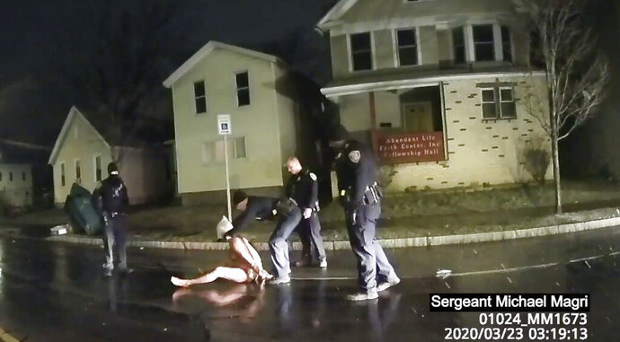 FILE- In this March 23, 2020 image made from police body camera video provided by Roth and Roth LLP, a Rochester police officer puts a hood over the head of Daniel Prude in Rochester, N.Y. Newly released emails show Rochester police commanders urged city officials to hold off on publicly releasing body camera footage of Daniel Prude's suffocation death because they feared violent blowback if the video came out during nationwide protests over the police killing of George Floyd. (Rochester Police via Roth and Roth LLP via AP, File)