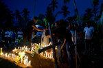 Relatives light candles after the burial of three victims of the same family, who died at Easter Sunday bomb blast at St. Sebastian Church in Negombo, Sri Lanka, Monday, April 22, 2019. Easter Sunday bombings of churches, luxury hotels and other sites was Sri Lanka's deadliest violence since a devastating civil war in the South Asian island nation ended a decade ago. (AP Photo/Gemunu Amarasinghe)