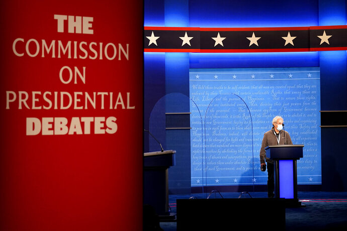 A member of the production crew stands at a podium near glass barriers to prevent the spread of COVID-19 on stage ahead of the final presidential debate between Republican candidate President Donald Trump and Democratic candidate former Vice President Joe Biden, Wednesday, Oct. 21, 2020, in Nashville, Tenn. The debate will take place Thursday, Oct. 22 at the Curb Event Center at Belmont University. (AP Photo/Julio Cortez)