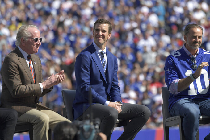 Former New York Giants quarterback Eli Manning smiles while he attends a ceremony to retire his jersey number 10 and celebrate his tenure with the team during half-time of an NFL football game against the Atlanta Falcons, Sunday, Sept. 26, 2021, in East Rutherford, N.J. (AP Photo/Bill Kostroun)