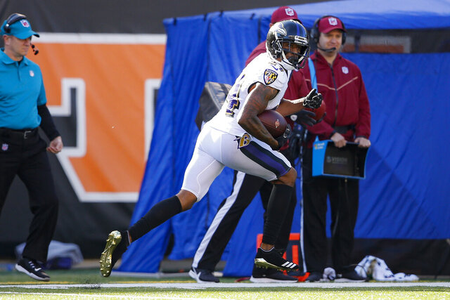 Baltimore Ravens cornerback Marcus Peters runs an interception in for a touchdown during the first half of NFL football game against the Cincinnati Bengals, Sunday, Nov. 10, 2019, in Cincinnati. (AP Photo/Gary Landers)