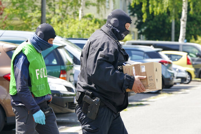 Federal police officers carry a box with secured documents during raids in Leipzig, Germany, Wednesday, May 27, 2020. Police in Germany have raided dozens of homes linked to anti-government groups suspected of manufacturing fake documents. (Peter Endig/dpa via AP)