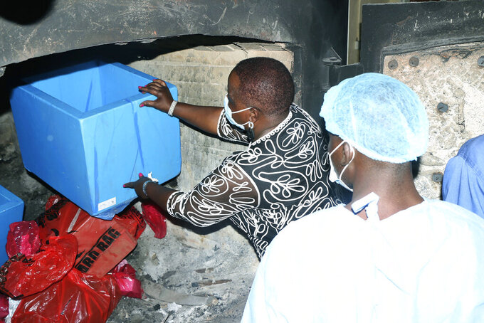 Malawi's Minister of Health Khumbize Chiponda, places COVID-19 vaccines in an incinerator, in Lilongwe, Malawi, Wednesday, May 19, 2021. Malawi has burned nearly 20,000 doses of AstraZeneca vaccines because they had expired. The government incinerated over 19,000 doses of the vaccine at Kamuzu Central Hospital in the capital Lilongwe. According to Health Secretary Charles Mwansambo the vaccines were the remainder of 102,000 doses that arrived in Malawi on March 26 with just 18 days until they expired on April 13. (AP Photo/Jacob Nankhonya)