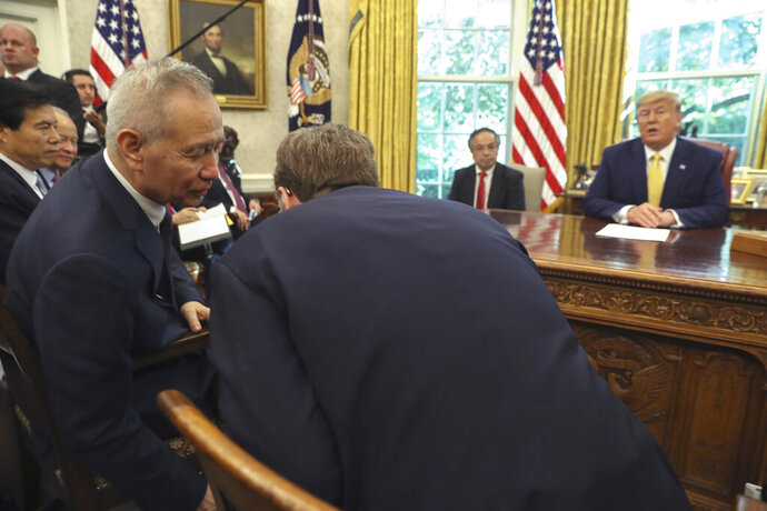 FILE - In this Friday, Oct. 11, 2019, file photo, President Donald Trump watches as Chinese Vice Premier Liu He speaks to U.S. Trade representative Robert Lighthizer, right, in the Oval Office of the White House in Washington. A truce in a U.S.-Chinese tariff war and Beijing's promises to open more of its state-dominated economy are raising hopes among investors. But China's own state media are trying to temper expectations, while companies express frustration about the halting pace of market opening. (AP Photo/Andrew Harnik, File)