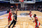 San Antonio Spurs guard Derrick White (4) goes up against New Orleans Pelicans guard Lonzo Ball, left, and forward Derrick Favors in the first half of an NBA basketball game in New Orleans, Wednesday, Jan. 22, 2020. (AP Photo/Gerald Herbert)