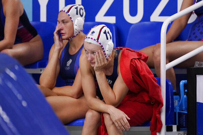Russian Olympic Committee players Evgeniya Ivanova (11) and Evgeniya Soboleva (10) watch from the bench during a loss to the United States in a semifinal round women's water polo match at the 2020 Summer Olympics, Thursday, Aug. 5, 2021, in Tokyo, Japan. (AP Photo/Mark Humphrey)