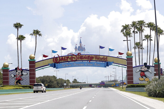 "Cars drive under a sign greeting visitors near the entrance to Walt Disney World, Thursday, July 2, 2020, in Lake Buena Vista, Fla. Despite a huge surge of Floridians testing positive for the new coronavirus in recent weeks, Magic Kingdom and Animal Kingdom, two of Disney World's four parks are reopening Saturday, July 11. When they do, visitors to ""The Most Magical Place on Earth"" will find new rules in place. (AP Photo/John Raoux)"