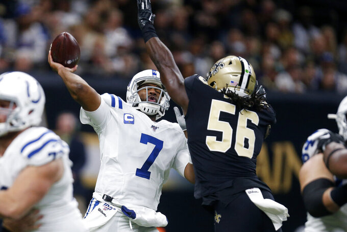 Indianapolis Colts quarterback Jacoby Brissett (7) passes under pressure from New Orleans Saints outside linebacker Demario Davis (56) in the first half of an NFL football game in New Orleans, Monday, Dec. 16, 2019. (AP Photo/Butch Dill)