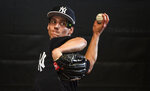 New York Yankees pitcher Danny Farquhar throws a bullpen session during baseball spring training Friday, Feb. 15, 2019, in Tampa, Fla. Farquhar is pitching with the Yankees after undergoing brain surgery for a ruptured aneurysm and must wear a special protective cap. (Thomas A. Ferrara/Newsday via AP)