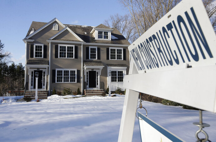 In this Thursday, Feb. 21, 2019 photo a sign is posted near a newly constructed home in Natick, Mass. On Thursday, March 14, the Commerce Department reports on sales of new homes in January. (AP Photo/Steven Senne)