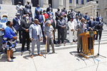 Rep. Robert Johnson, D-Natchez, Democratic leader of the House and flanked by party lawmakers and members of the Mississippi Legislative Black Caucus, stands at the podium as he says the state flag does not unify Mississippi, and calls on the Legislature to vote for a new flag this session, during a news conference in front of the Capitol in Jackson, Miss., Tuesday, June 23, 2020. (AP Photo/Rogelio V. Solis)