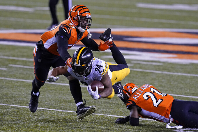 Pittsburgh Steelers' Benny Snell (24) is tackled by Cincinnati Bengals' Mackensie Alexander (21) and Germaine Pratt (57) during the second half of an NFL football game, Monday, Dec. 21, 2020, in Cincinnati. (AP Photo/Michael Conroy)
