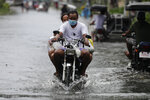 Residents on a motorcycle negotiate a flooded road due to Typhoon Molave in Pampanga province, northern Philippines, Monday, Oct. 26, 2020. A fast-moving typhoon forced thousands of villagers to flee to safety in provinces south of the Philippine capital Monday, flooding rural villages and ripping off roofs, officials said. (AP Photo/Aaron Favila)