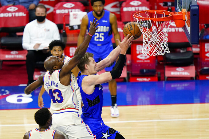 Orlando Magic's Moritz Wagner, right, goes up for a shot against Philadelphia 76ers' Anthony Tolliver during the second half of an NBA basketball game, Sunday, May 16, 2021, in Philadelphia. (AP Photo/Matt Slocum)