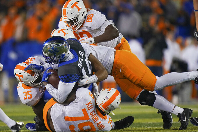 Kentucky running back Asim Rose (10) is tackled by several Tennessee defenders during the second half of an NCAA college football game Saturday, Nov. 9, 2019, in Lexington, Ky. (AP Photo/Bryan Woolston)