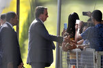 Photographed through a fence, Brazilian President Jair Bolsonaro greets supporters as he leaves the presidential residence, Alvorada Palace, in Brasilia, Brazil, Friday, March 19, 2021. (AP Photo/Eraldo Peres)