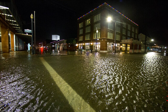 Water rises from the storm surge of Tropical Storm Beta in The Strand as the storm moves toward landfall, late Monday, Sept. 21, 2020, in Galveston, Texas. (Brett Coomer/Houston Chronicle via AP)