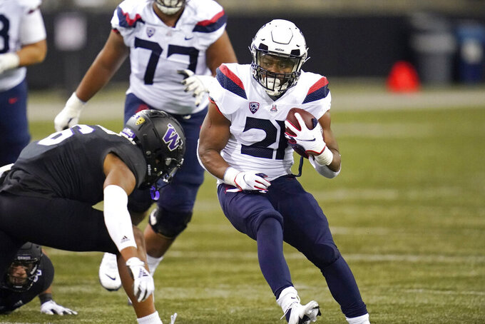 Arizona's Jalen John carries the ball against Washington during the second half of an NCAA college football game Saturday, Nov. 21, 2020, in Seattle. Washington won 44-27. (AP Photo/Elaine Thompson)