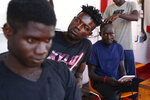 Migrants get their hair shaved aboard the Ocean Viking humanitarian rescue ship, in the Mediterranean Sea, Thursday, Sept. 12, 2019. Eighty-two rescued migrants remain on board the humanitarian rescue ship waiting for a European country to give them permission to disembark. (AP Photo/Renata Brito)