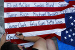 A protester at an encampment outside City Hall, Friday, June 26, 2020, in New York writes the names of individuals killed in incidents involving police. (AP Photo/John Minchillo)