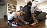 Tiffany Favre, left, and her son, Brandon, use blocks to raise their couch off the floor Friday, July 12, 2019, in Baton Rouge, La., ahead of Tropical Storm Barry. The National Weather Service in New Orleans says water is already starting to cover some low lying roads as Tropical Storm Barry approaches the state from the Gulf of Mexico. (AP Photo/David J. Phillip)