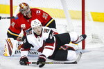 Arizona Coyotes' Carl Soderberg, right, crashes over the pads of Calgary Flames goalie David Rittich during the first period of an NHL hockey game, Tuesday, Nov. 5, 2019 in Calgary, Alberta.  (Jeff McIntosh/Canadian Press via AP)
