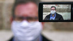 While wearing protective mask due to the COVID-19 outbreak, Jim Howard, a drama teacher at Westwood, Mass., High School, is interviewed outside the school's auditorium after working with students on a virtual performance of Shakespeare's