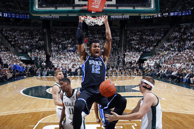 Duke's Javin DeLaurier (12) dunks between Michigan State's Thomas Kithier, right, and Aaron Henry (11) during the first half of an NCAA college basketball game Tuesday, Dec. 3, 2019, in East Lansing, Mich. Duke won 87-75. (AP Photo/Al Goldis)