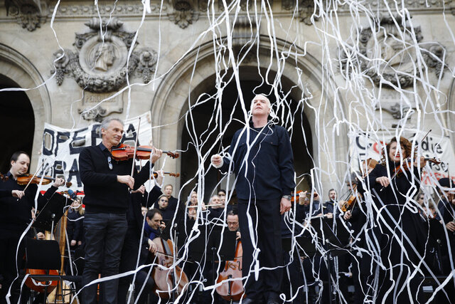 Michel Dietlin, center, stands with musicians of the orchestra outside the Palais Garnier opera house after performing Saturday, Jan. 18, 2020 in Paris. As some strikers return to work, with notable improvements for train services that have been severely disrupted for weeks, more radical protesters are trying to keep the movement going. (AP Photo/Kamil Zihnioglu)