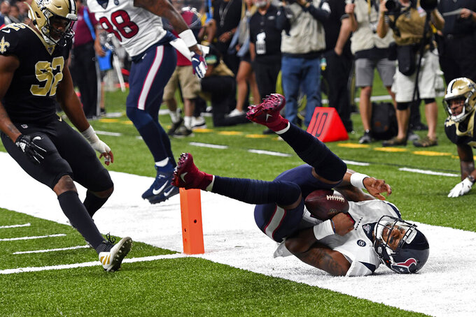 Houston Texans quarterback Deshaun Watson (4) hits his head on the turf as he scores a touchdown, as New Orleans Saints defensive end Marcus Davenport (92) pursues in the first half of an NFL football game in New Orleans, Monday, Sept. 9, 2019. (AP Photo/Bill Feig)