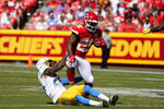 Kansas City Chiefs' Clyde Edwards-Helaire (25) is tackled by Los Angeles Chargers' Nasir Adderley (24) during the second half of an NFL football game, Sunday, Sept. 26, 2021, in Kansas City, Mo. (AP Photo/Ed Zurga)