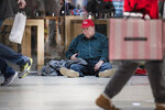 Jefrey Wojtisek sits on the floor as he awaits for the Apple store to open their doors on Black Friday at the King of Prussia Mall in King of Prussia, Pa. Friday, Nov. 28, 2019. (Jose F. Moreno/The Philadelphia Inquirer via AP)