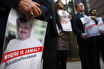 Alyssa Edling, center, and Thomas Malia, second from right, both with PEN America, join others as they hold signs of missing journalist Jamal Khashoggi, during a news conference about his disappearance in Saudi Arabia, Wednesday, Oct. 10, 2018, in front of The Washington Post in Washington. (AP Photo/Jacquelyn Martin)