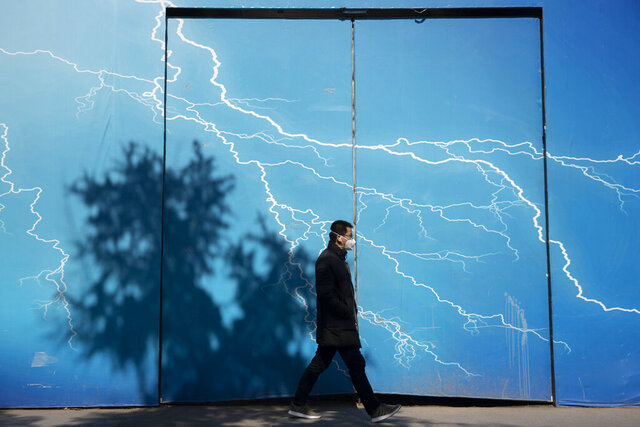 A man wearing a mask walks past a billboard depicting lightning in Beijing on Wednesday, March 4, 2020. The mushrooming outbreaks in other countries contrasted with optimism in China, where thousands of recovered patients were going home and the number of new infections dropped to the lowest level in more than six weeks. (AP Photo/Ng Han Guan)