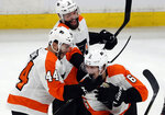 Philadelphia Flyers defenseman Travis Sanheim (6) celebrates his winning goal with teammates Phil Varone (44) and Radko Gudas (3) after an NHL hockey game against the Boston Bruins, Thursday, Jan. 31, 2019, in Boston. (AP Photo/Elise Amendola)