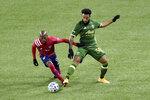 FC Dallas forward Fafa Picault, left, goes after a ball with Portland Timbers midfielder Eryk Williamson during the first half of an MLS soccer match in Portland, Ore., Sunday, Nov. 22, 2020. (AP Photo/Steve Dykes)