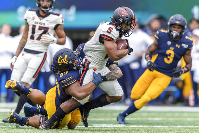 Oregon State wide receiver Kolby Taylor (5) is tackled by California  nose tackle Luc Bequette (93) in the second quarter of an NCAA college football game in Berkeley, Calif., Saturday, Oct. 19, 2019. (AP Photo/John Hefti)