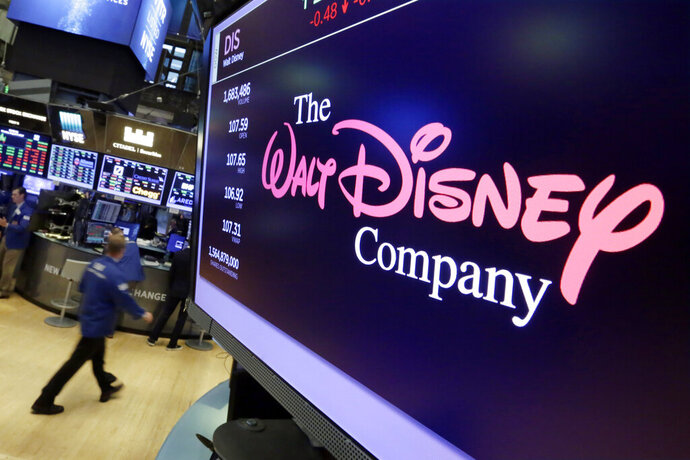 FILE - In this Aug. 8, 2017, file photo, The Walt Disney Co. logo appears on a screen above the floor of the New York Stock Exchange. Disney's new streaming service, Disney Plus, is adding a disclaimer to