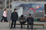 In this Nov. 26, 2019, photo, men wait for public transport near a propaganda photo showing North Korean 'soldiers-builders' in downtown Pyongyang, North Korea. North Korean leader Kim Jong Un and U.S. President Donald Trump have signaled their affection for each other so regularly it might be easy to miss rising fears that the head-spinning diplomatic engagement of the past two years is falling apart. (AP Photo/Dita Alangkara)