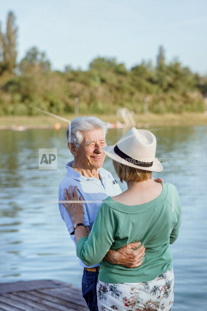 Senior man looking at woman wearing hat on jetty by lake
