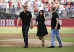 Britain's Prince Harry, left, and Meghan, Duchess of Sussex, walk off the field before a baseball game between the Boston Red Sox and the New York Yankees, Saturday, June 29, 2019, in London. Major League Baseball makes its European debut game today at London Stadium. (AP Photo/Tim Ireland)