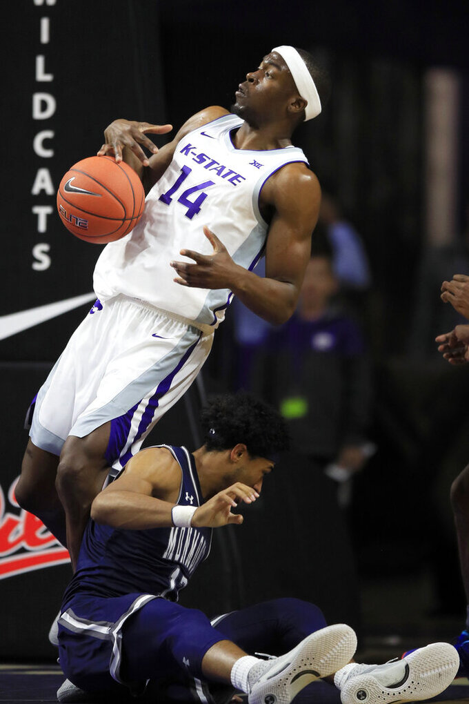 Kansas State forward Makol Mawien (14) rebounds next to Monmouth guard Marcus McClary, bottom, during the first half of an NCAA college basketball game in Manhattan, Kan., Wednesday, Nov. 13, 2019. (AP Photo/Orlin Wagner)
