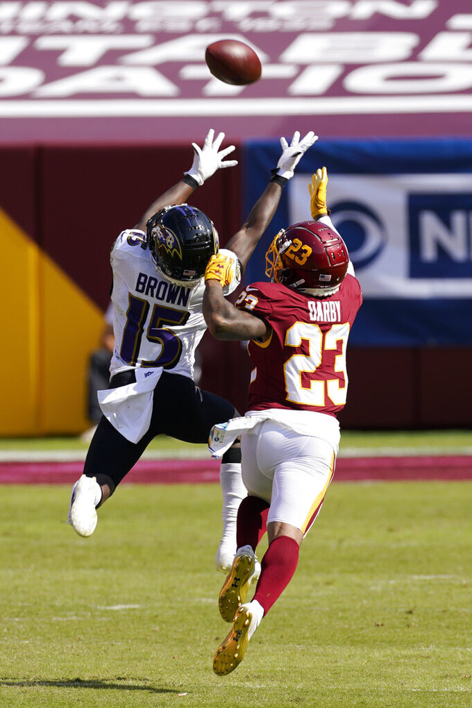 Baltimore Ravens wide receiver Marquise Brown (15) reaches for a pass as Washington Football Team cornerback Ronald Darby (23) defends during the first half of an NFL football game Sunday, Oct. 4, 2020, in Landover, Md. (AP Photo/Steve Helber)