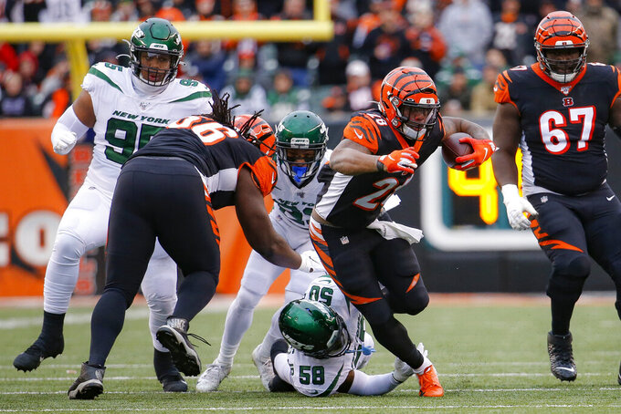 Cincinnati Bengals running back Joe Mixon (28) breaks a tackle by New York Jets outside linebacker James Burgess (58) during the first half of an NFL football game, Sunday, Dec. 1, 2019, in Cincinnati. (AP Photo/Frank Victores)