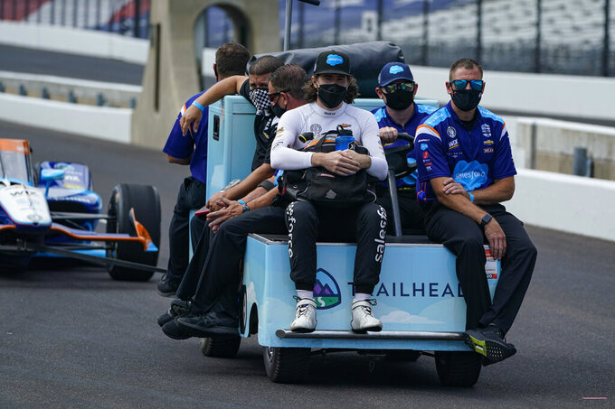 J.R. Hildebrand, left foreground, rides out to the pit area with his team during practice for the Indianapolis 500 auto race at Indianapolis Motor Speedway in Indianapolis, Friday, Aug. 14, 2020. (AP Photo/Michael Conroy)
