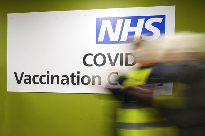 FILE - In this Thursday, Jan. 14, 2021 file photo, a sign in the interior of the NHS vaccination centre in Robertson House, Stevenage, England. An Italian man living in Berlin has on Friday Feb. 26, 2021 been convicted of attempted extortion for threatening to blow up a British National Health Service hospital unless he was paid off with 10 million pounds ($13.2 million) in crypto currency. Defendant Emil A., whose last name wasn't given in line with German privacy laws, was sentenced to three years in prison.(Leon Neal/Pool Photo via AP, file)