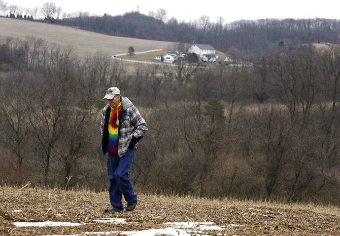 In this Saturday, Feb. 23, 2019 photo, Mike Carpenter, uncle of Greg Longenecker, walks the field where Longenecker was killed by a bulldozer in 2018, in Bernville, Pa. A federal lawsuit accuses Pennsylvania State Police of gross recklessness for using a bulldozer to chase and inadvertently run over and kill Longenecker, who had fled after being caught growing marijuana on public land. (AP Photo/Jacqueline Larma)