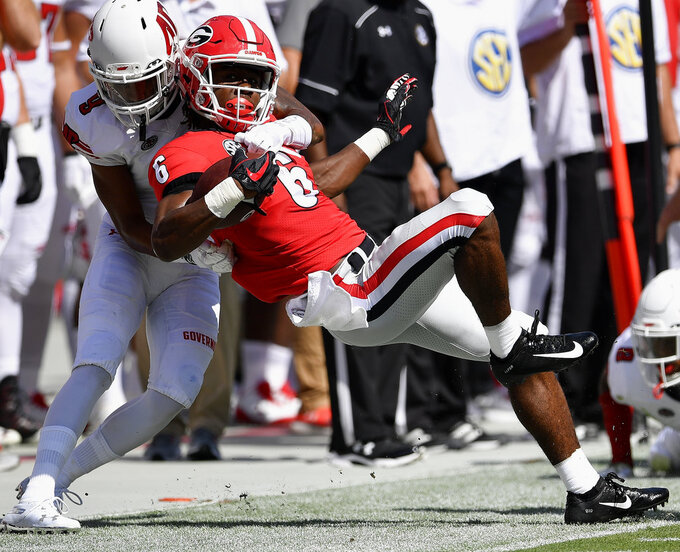 Austin Peay defensive back Trent Taylor (9) tackles Georgia running back James Cook (6) during the first half of an NCAA college football game, Saturday, Sept. 1, 2018, in Athens, Ga. (AP Photo/Mike Stewart)