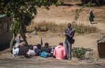A preacher reads from the Bible to people as they sit on top of a large rock on the outskirts of Harare, Zimbabwe Sunday, Sept. 8, 2019. Former president Robert Mugabe, who enjoyed strong backing from Zimbabwe's people after taking over in 1980 but whose support waned following decades of repression, economic mismanagement and allegations of election-rigging, is expected to be buried next Sunday, state media reported. (AP Photo/Ben Curtis)